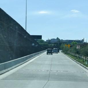 La route délimitée par un mur et des clôtures.