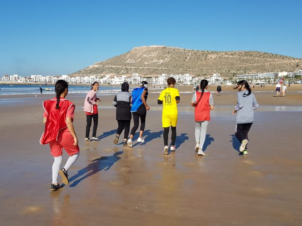 Moroccan girls jogging on Agadir beach