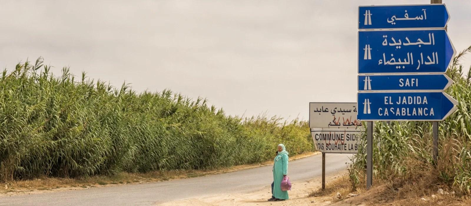 Une femme attendant au coin d'une rue au Maroc - Les Routes du Monde