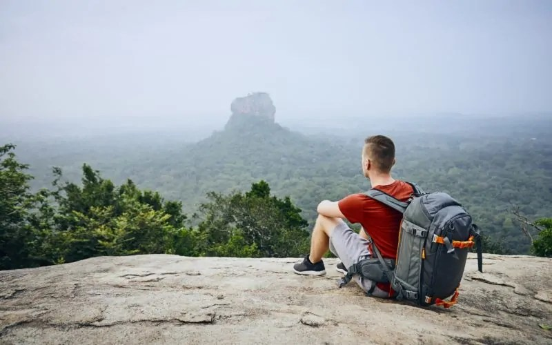 Young man with backpack against Sigiriya Rock (UNESCO World Heritage Site). View from Pidurangala Rock in Sri Lanka.