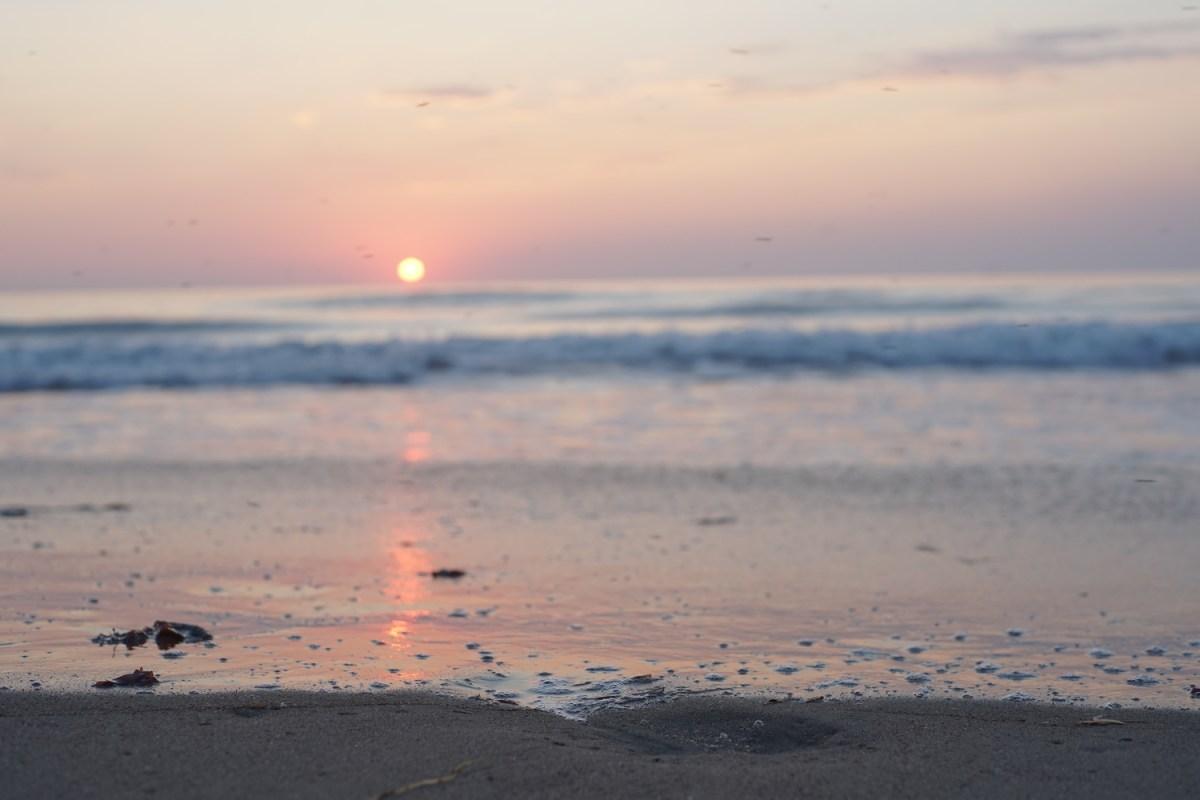 setting sun over a reddened beach