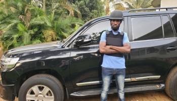 Bobi Wine standing besides his newly acquired armored car