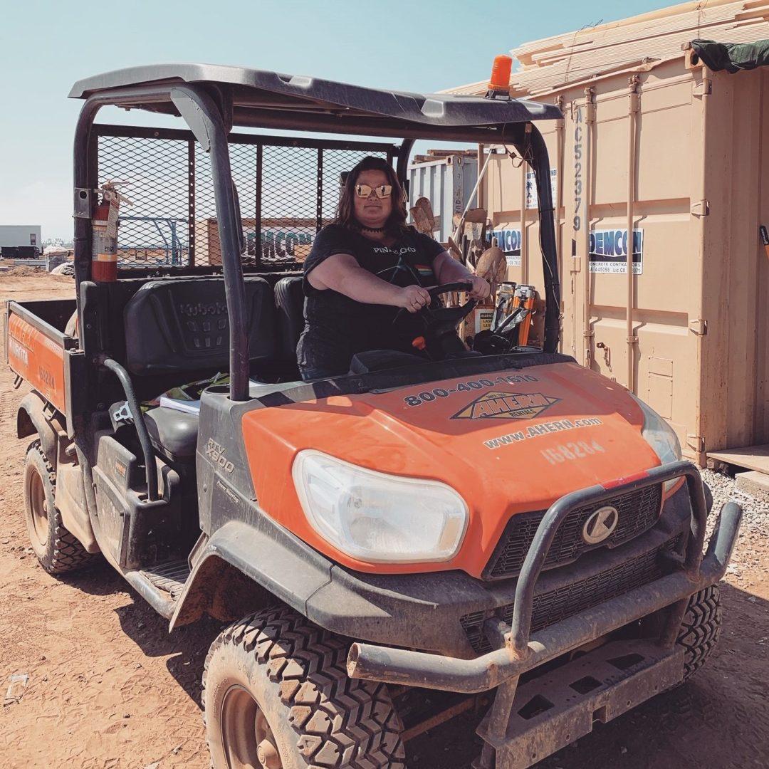 Employee driving jobsite equipment.