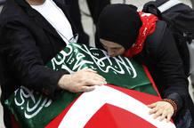 Cigdem Topcuoglu, viuda de uno de los activistas turcos asesinados, llora sobre el ataúd de su marido.