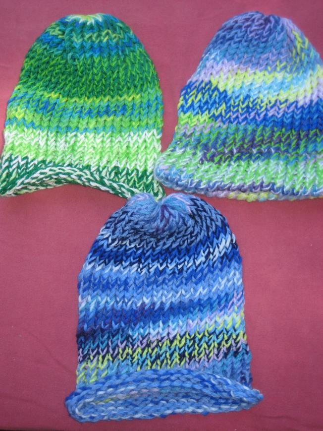 These large green and blue hats cost $13 each, including shipping. The one on the upper right has a finished edge. The other two have rolled edges.