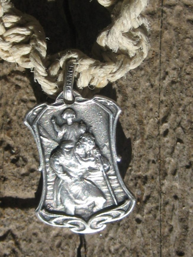 Here's a closeup of the front of the medal. I suppose that's the Christ Child being carried by St. Christopher.
