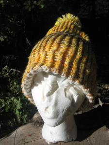 In this photo, Esmerelda is modeling a large hat with a finished edge. The edge is folded down in this view. It's a bright hat with lots of shades of oranges and yellow. The hat is topped with a pompom and costs $13, including shipping.