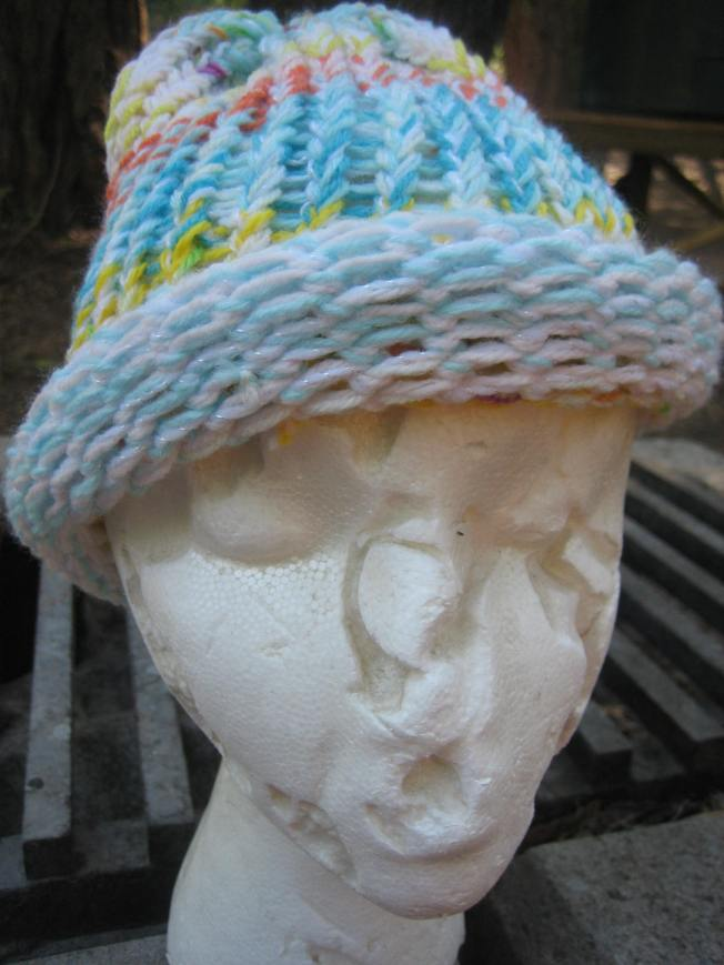 This photo shows another large hat with an unfinished edge featuring a variety of colors. The hat is mostly a light blue, but it also includes orange and yellow. The price is $13, including shipping.