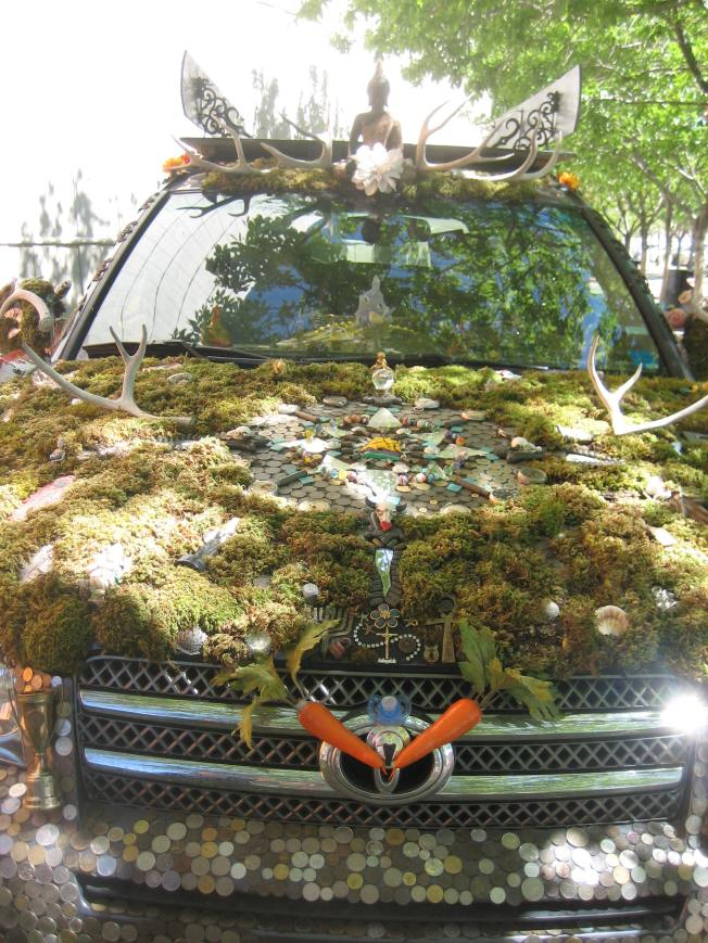 Front view of an art car covered with moss and coins and antlers and all sorts of little things.
