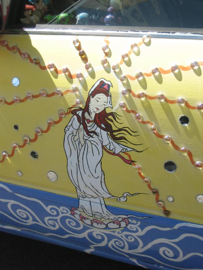 Art car JGURL has painting of Kwan Yin on the side. Sunlight is lighting her face and head. Glass beads radiate out from her head.