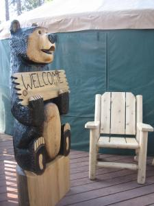 A carved wooden bear holds a welcome sign. It and a wooden chair sit on a wooden deck in front of a yurt.