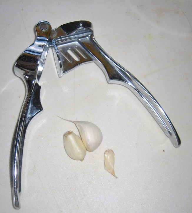 Metal garlic press with three gloves of garlic