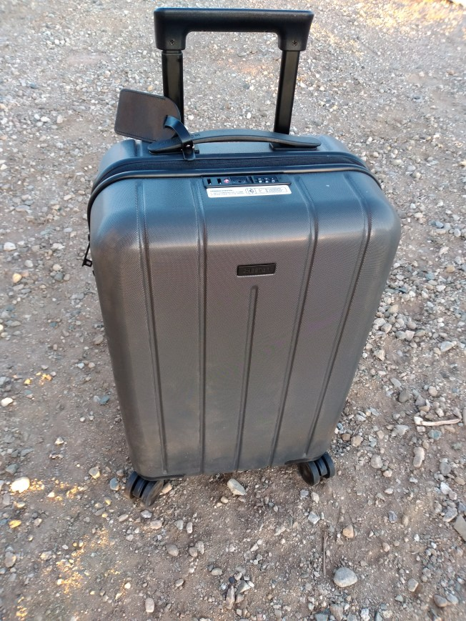 Black carry-on bag with wheels stands on pebbly ground