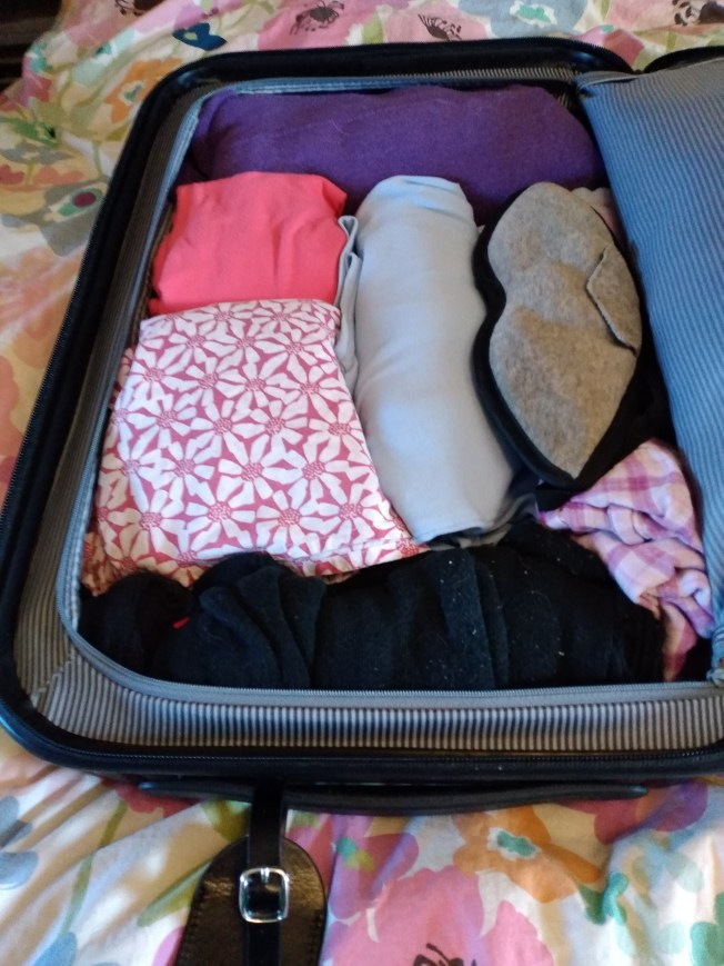 One side of suitcase is packed full of clothes.