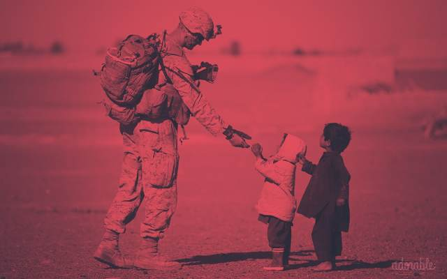 Two children giving food to a soldier