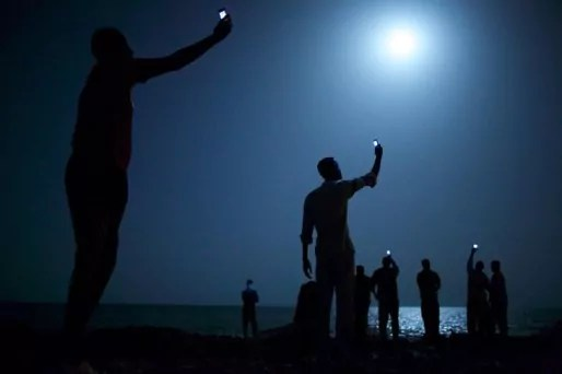 """World Press 2014 - 26 février 2013, Djibouti. Des migrants africains tentent de capter le réseau téléphonique somalien (moins cher) depuis Djibouti, pour joindre leurs proches. Crédits : JOHN STEINMEYER/VII POUR """"NATIONAL GEOGRAPHIC""""."""