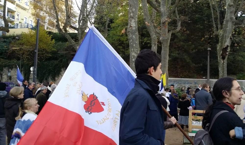 """Le rassemblement des cathos tradis pour """"sauver"""" l'église Saint-Bernard. Des drapeaux français ornés du """"cœur sacré de Jésus"""" ont été distribués aux participants. ©LB/Rue89Lyon"""