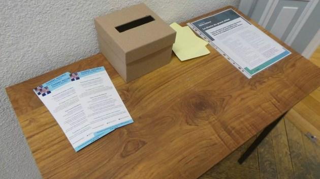 A la sortie de la salle accueillant le grand débat sont disposés sur une table une boite à idée, les règles du débat et des tracts pour Thierry Michels.