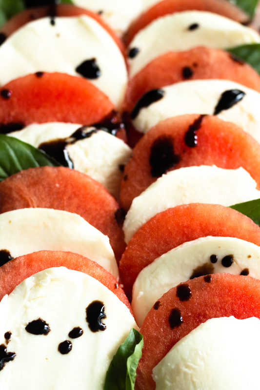 close up of watermelon and mozzarella slices with balsamic drizzle