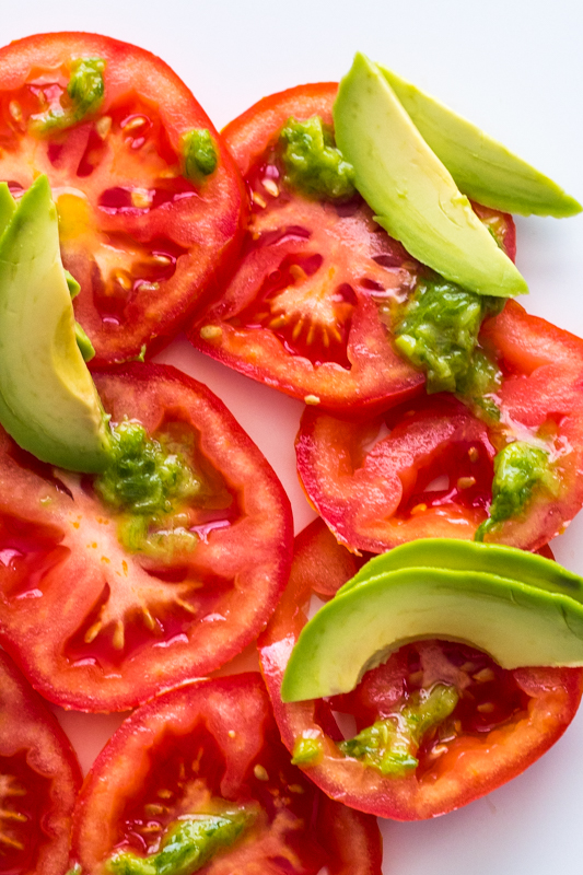 close up of sliced tomatoes with avocado and a green sauce