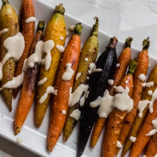 rainbow roasted carrots with tahini sauce drizzled on top