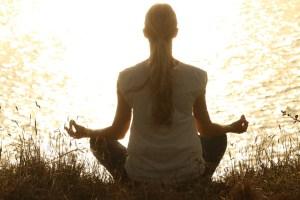 woman meditating by lake