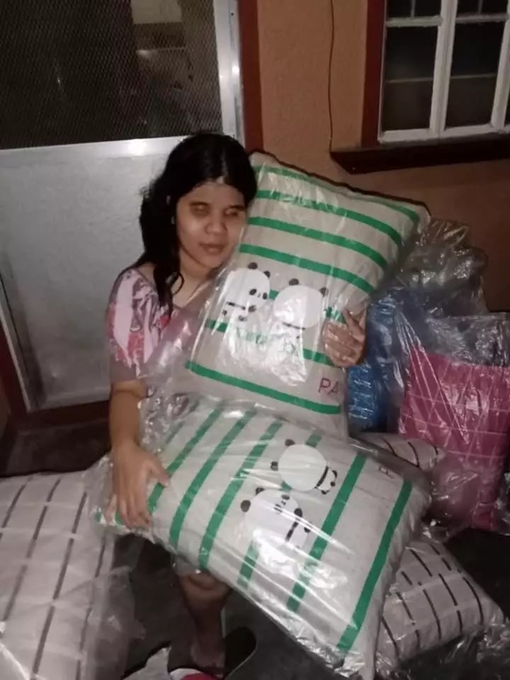 Blind woman with pillows she sells online.