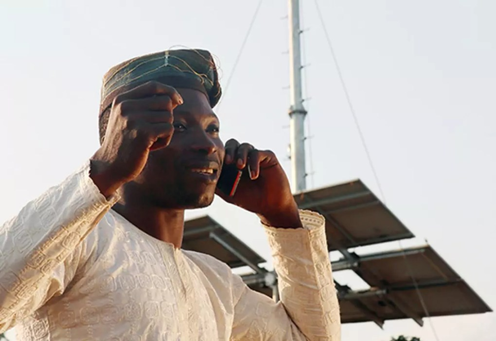 Man in Africa using cellphone in front of antenna.