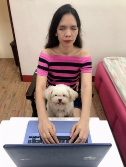 Jasmin Ambiong using a laptop with a dog in her lap.