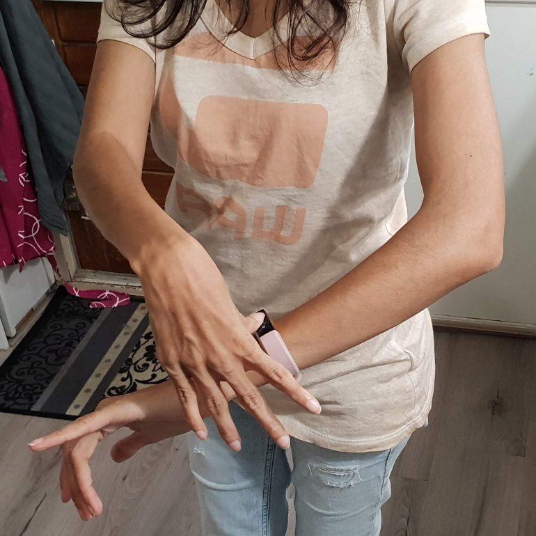 Bediening van de Fitbit Alta HR door te tikken met mijn duim.