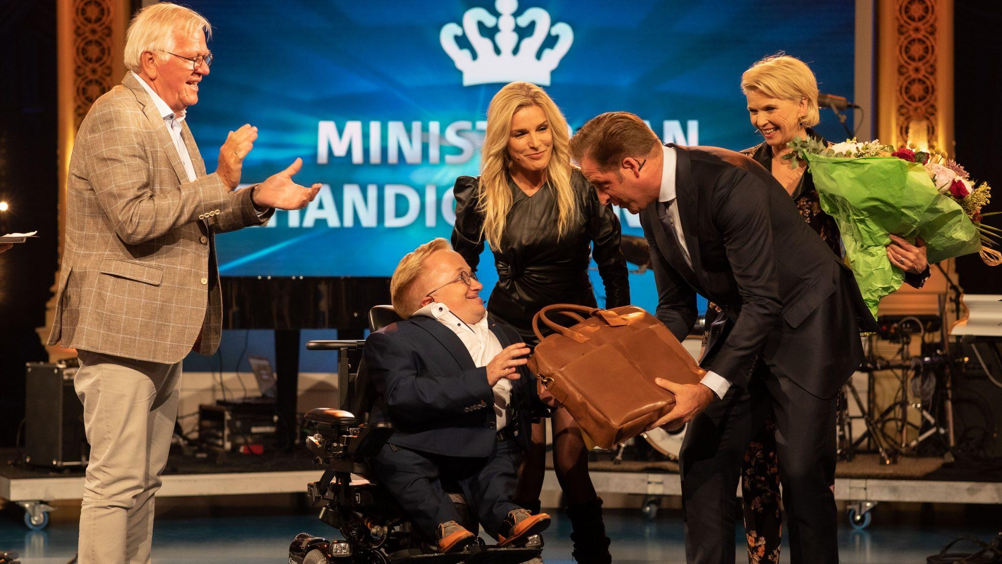 Rick is de nieuwe minister van gehandicaptenzaken en neemt zijn prijs in ontvangst.