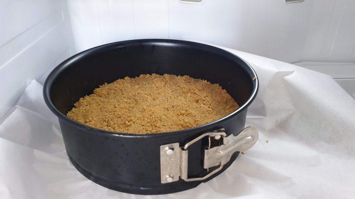 Bodem van koekkruimels en boter in een springvormin de koelkast.