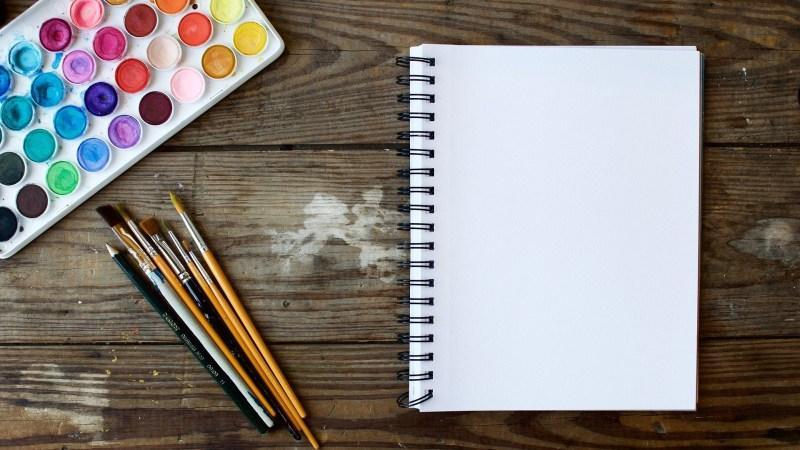 Blog: Een leeg tekenblok met kwasten en waterverf in allerlei kleuren.