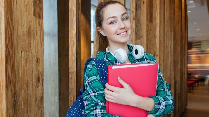 Meisje op school aan het begin van een nieuw schooljaar met een map in haar handen en een koptelefoon om haar nek.