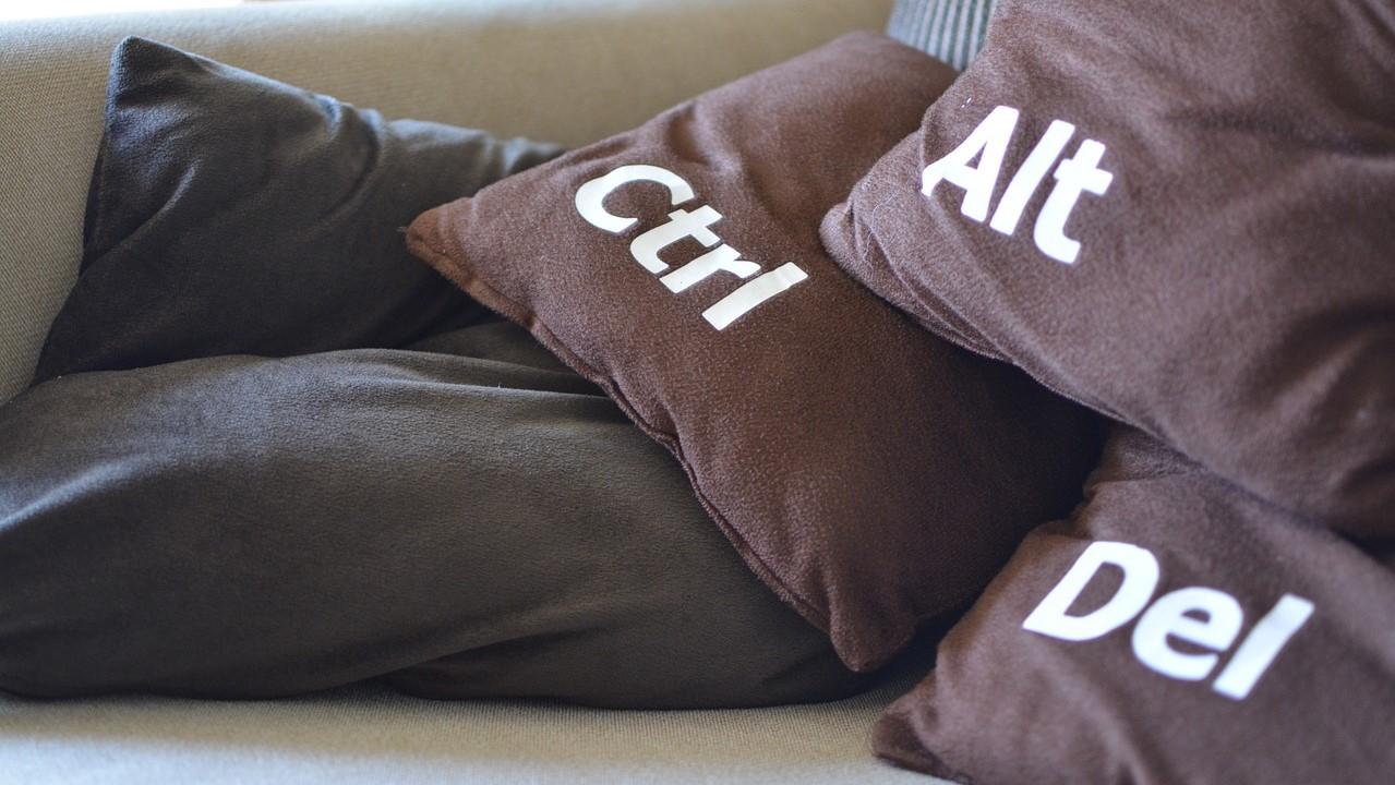 Opnieuw beginnen: 3 bruine kussens met de toepasselijke tekst: Alt Ctrl Del