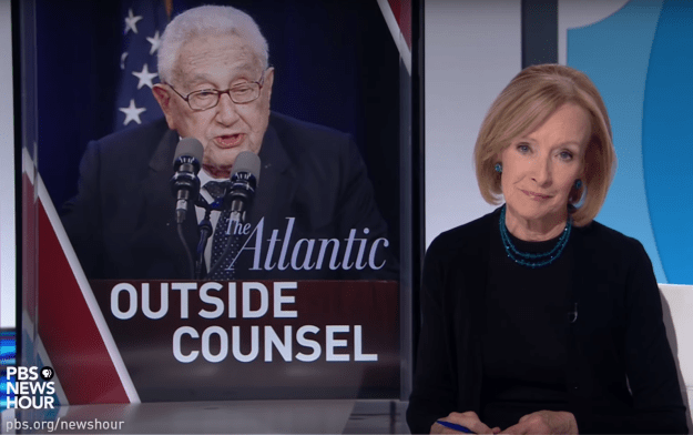 Judy Woodruff sits in front of image of Henry Kissinger