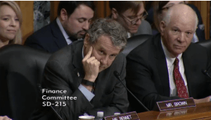 Senator Brown leans on his hand during questioning
