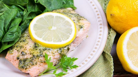 Salmon with a lemon slice and salad on a white plate.