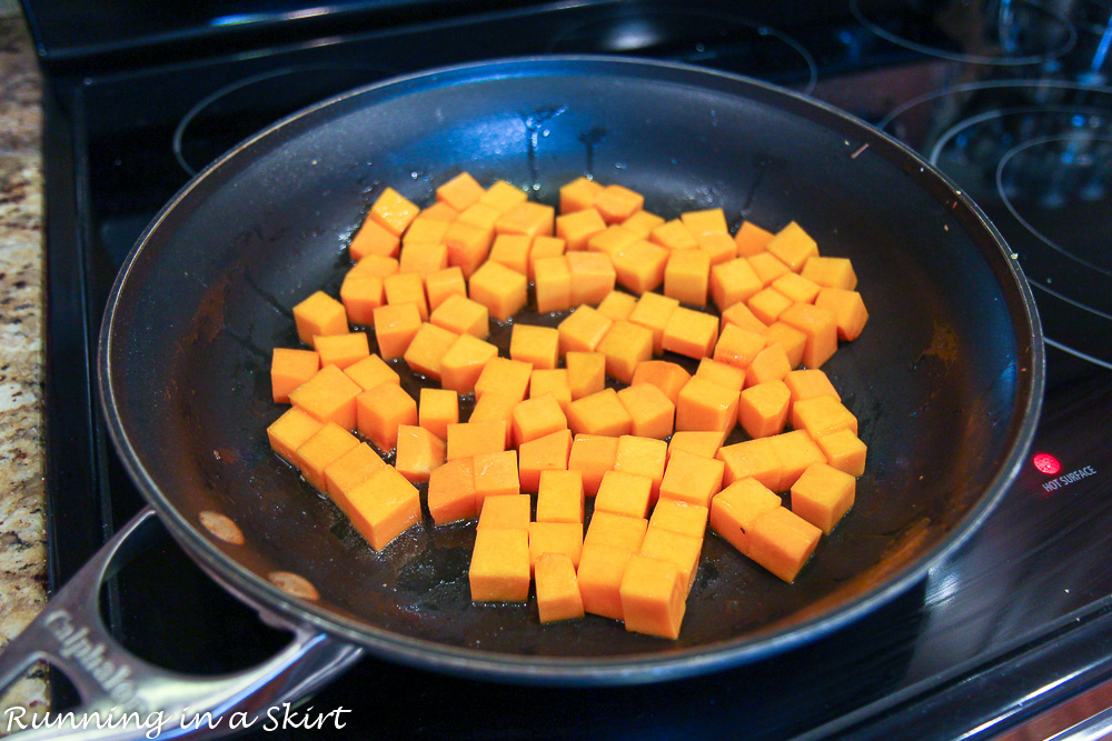 Butternut squash cooking in a pan on the stove top.