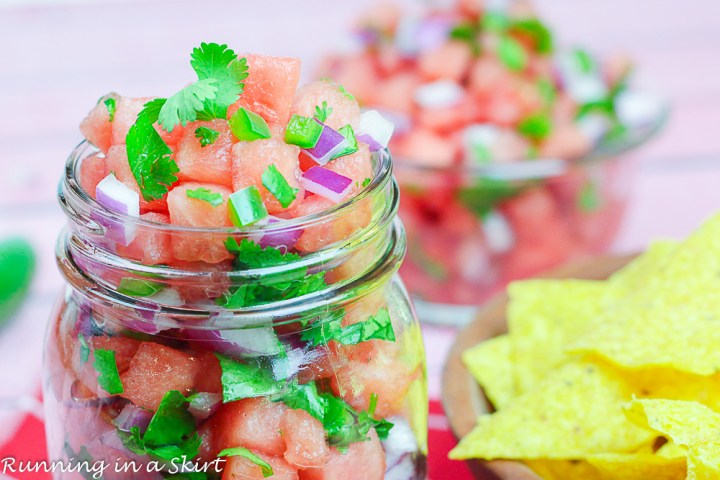 Glass jar with salsa and wooden bowl with chips.