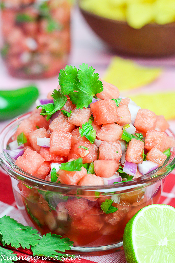 Watermelon salsa is a glass bowl with chips in the background.
