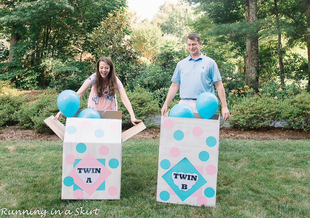 Blue balloons coming out of boxes at a twin gender reveal with Mom and Dad opening boxes.