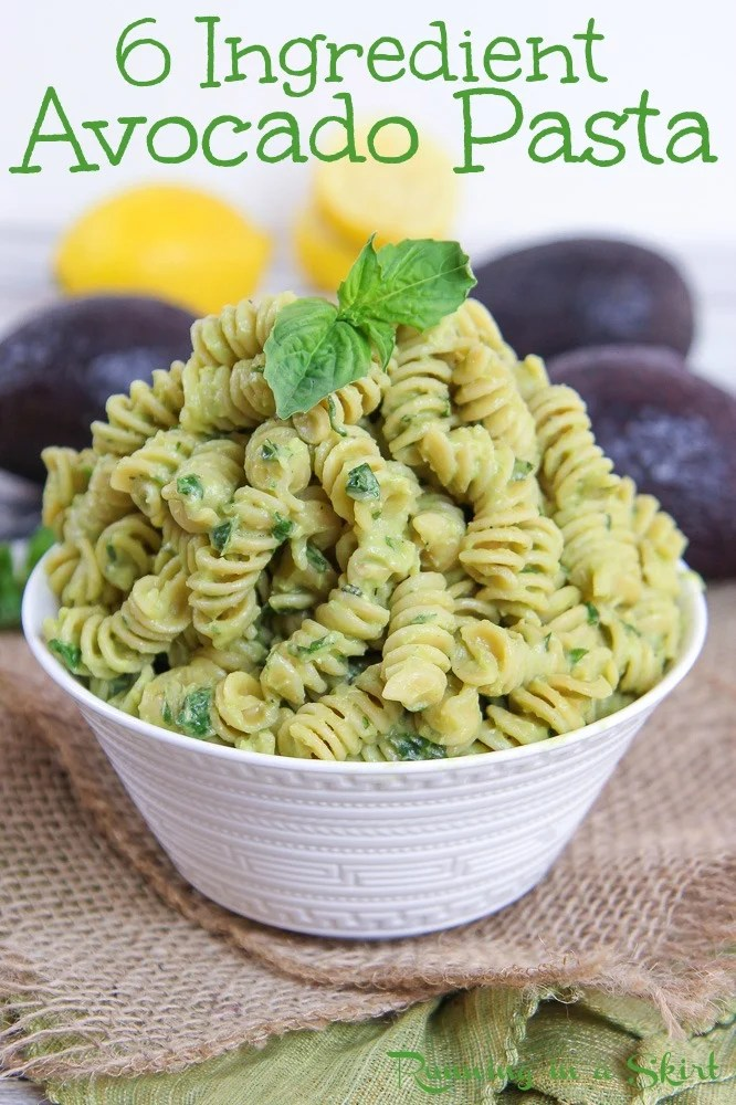 Bowl of creamy avocado pasta with avocado and lemon in the background.