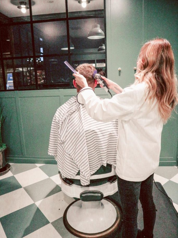 His and Hers Pampering at the Adolphus. Man getting his head shaved by woman barber.