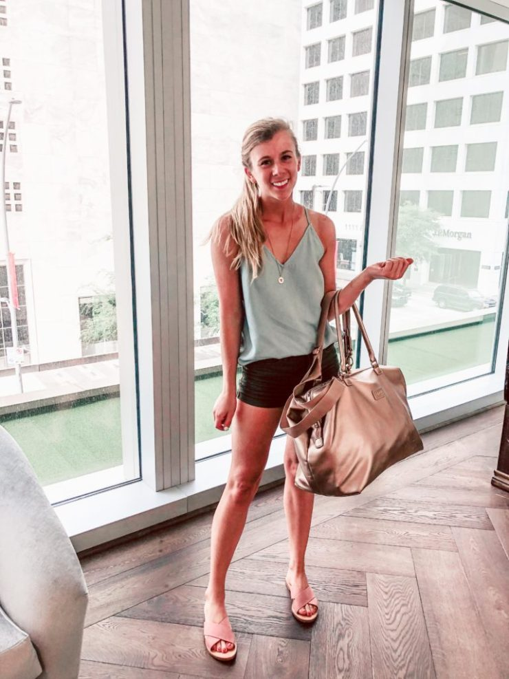 Getting Concert Ready with Palm Beach Tan: Blonde Dallas Blogger, Running in HeelsGetting Concert Ready with Palm Beach Tan: Blonde Dallas Blogger, Running in Heels stands in Hotel wearing chambray tank top from Loft, army green shorts from H&M, and pink criss cross sandals from ZooShoo. She carries the perfect pink gold Lipault weekender bag to finish out the look.