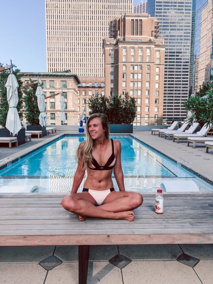 Where to stay in Houston: Hotel Alessandra   Dallas blogger, Running in Heels sits poolside wearing a pink and black bikini from Adore me with Bai juice next to her.