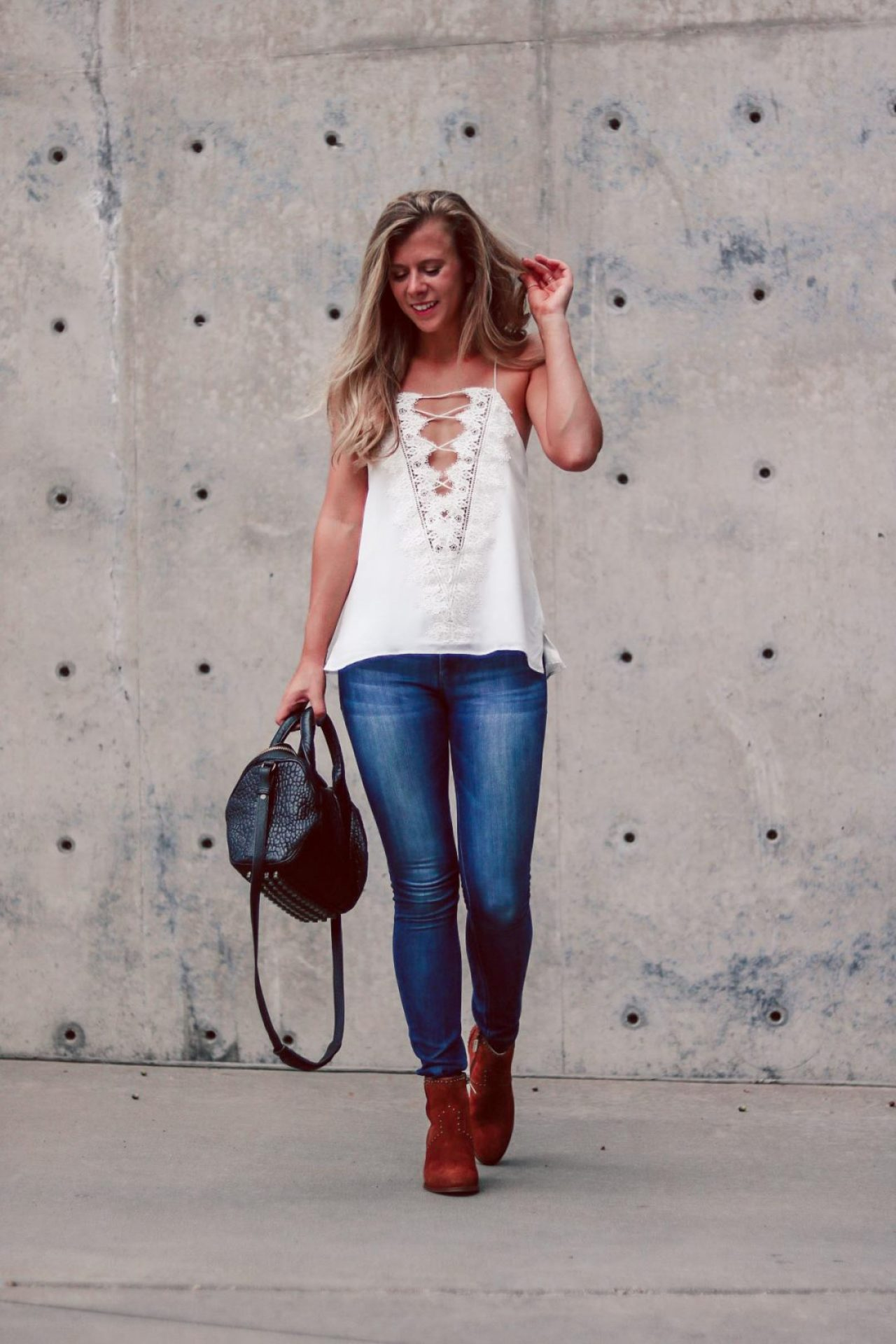 Lace-Up Cami Comparison | Running in Heels | Blonde wearing lace-up cami by Cami NYC in white, DL1961 denim, and Italeau booties while carrying an ALexander Wang Rockie bag.