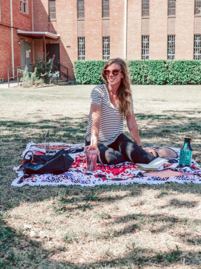 Girl sitting on blanket on lawn with computer, books, and Stok iced coffee