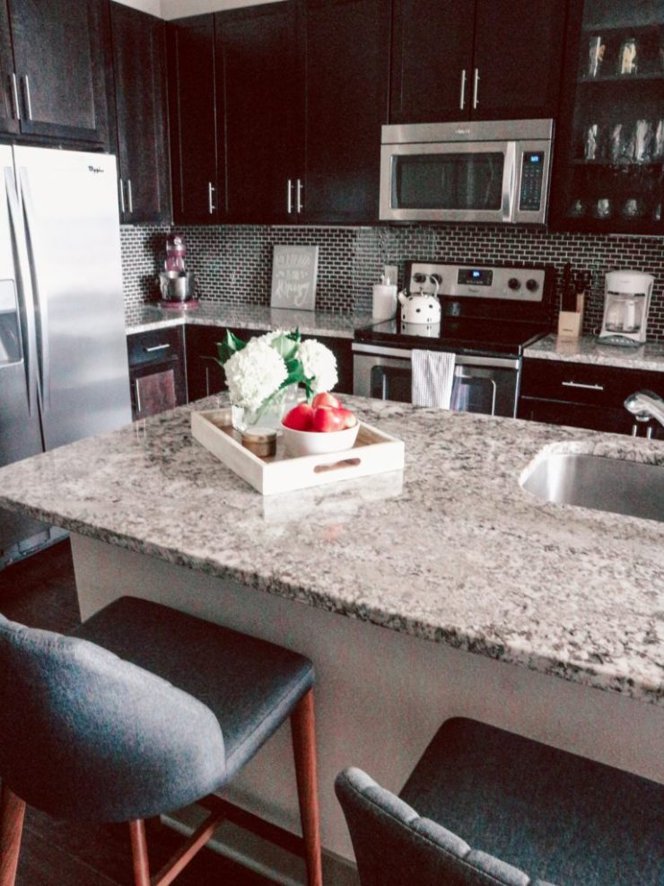 How to Choose Barstools- Because You Don't Need a Kitchen Table | Styled Kitchen Counter with granite kitchen Island with white try filled with hydrangas, bowl of apples, and Craft + Foster candle. Showing grey APT2B barstools in front of wine rack.