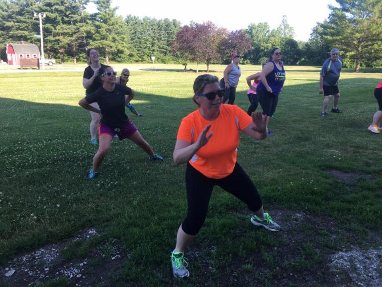 The group doing strength and stretches in the Running Wild 5K Race Warm Up, Led by Coach Amie
